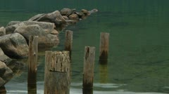 Gentle Lake Surface with Rocky Point and Old Wooden Posts (zoom out) Stock Footage