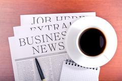 Business newspaper, notebook and cup of coffee Stock Photos