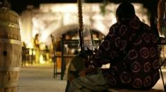 Musician plays strum instrument on Isola Tiberina Stock Footage