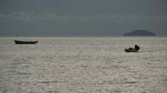 Asian Fisherman Paddles His Boat Into Shore Stock Footage