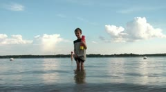 Boy in Lake Squirts Water with Toy Stock Footage