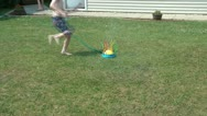 Boy Running Through Sprinkler Stock Footage