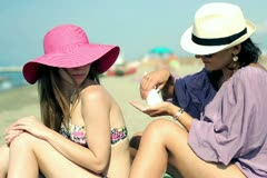 Young female friends applying sunlotion on the beach Stock Footage
