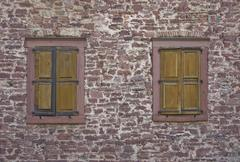 Stone wall with old windows Stock Photos