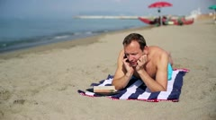 Man relaxing on the beach and talking on a cell phone - stock footage