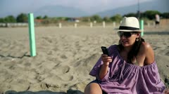 Attractive woman sitting on the beach and texting message Stock Footage