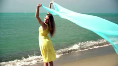 Young woman with waving sarong at the beach, slow motion Stock Footage