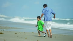 Latin American father enjoying kicking ball with kid on beach  Stock Footage