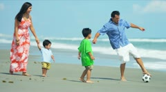 Latin American parents walking on beach playing football with children Stock Footage