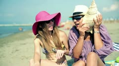 Beautiful female friends sitting on the beach with seashell Stock Footage