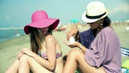 Stock Video Footage of Young female friends applying sunlotion on the beach