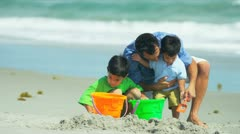 Stock Video Footage of Latin American boys building sand castles with father on summer beach