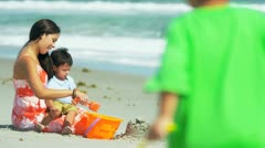 Young Hispanic family playing together on beach  Stock Footage