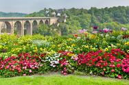 Stock Photo of bright flowerbed and tall stone bridge
