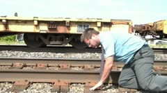 Businessman Puts Ear to Railroad Track Stock Footage