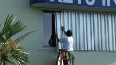 Hurricane shutters preparation - stock footage