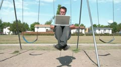 Businessman Swinging at Playground Stock Footage