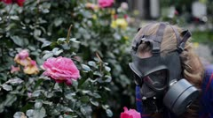 girl in gas masks smells roses - stock footage