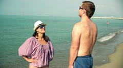 Young happy couple standing on the beach and talking Stock Footage