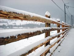 Wooden fence covered by snow Stock Photos