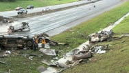 Destroyed trucks and cars litter a highway from a passing tonado Stock Footage