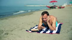 Young man relaxing on the beach Stock Footage