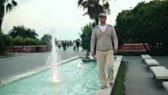 Handsome man walking by fountain in the city, slow motion Stock Footage