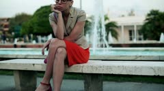 Young sad woman sitting along on a bench, outdoors, slow motion Stock Footage