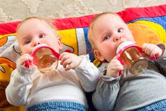 Babies eating from bottle Stock Photos