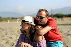 Portrait of smiling couple sitting on beach and talking Stock Footage