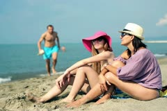 Group of friends with huge shell sitting on the beach Stock Footage