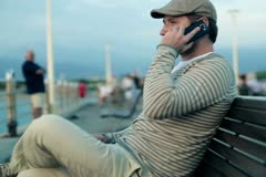 Happy young man sitting on bench and talking on cellphone, outdoors - stock footage