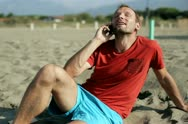 Handsome young man sitting on the beach and talking on cellphone Stock Footage