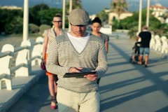 Young man with tablet walking along pier, women in background Stock Footage
