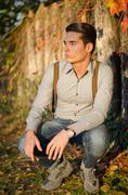 handsome young man  in fall (autumn) in front of wood fence - stock photo