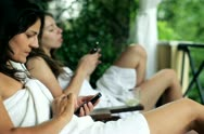 Two women with cellphones relaxing on balcony, steadicam shot Stock Footage