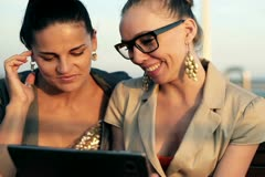 Two ladies with tablet computer sitting on bench, steadycam shot Stock Footage