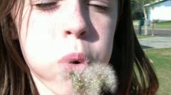 Girl Blows Dandilion Seeds at Camera Stock Footage