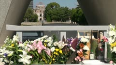 Cenotaph, flowers, 'Flame of Peace', and 'Atomic Bomb Dome' in Hiroshima - stock footage