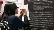 Schoolkids take notes in the Peace Memorial Museum in Hiroshima Stock Footage