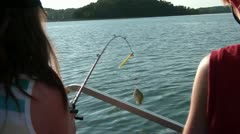 Girl Pulls in Fish from Boat Stock Footage