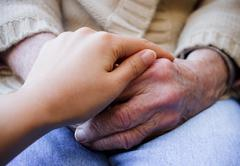 young caregiver holding senior's hands - stock photo