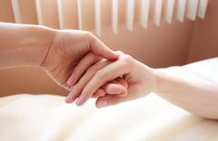 holding hand of a sick loved one - stock photo