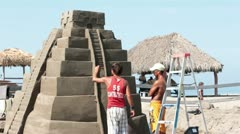 Friends building large Mayan Temple of sand at Resort HD 4107 Stock Footage
