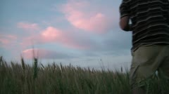Man in Wheat Field Watching Colored Clouds Stock Footage