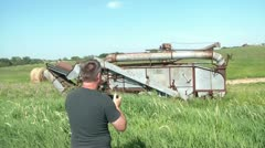 Guy Taking Pictures of Rural Farm Equipment Stock Footage