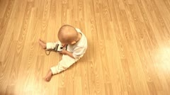 Baby on floor playing with a photo camera Stock Footage
