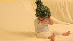 Cute baby wearing green fez sitting on sofa Stock Footage