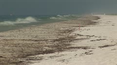 BP Oil Spill washes up on white sandy beach Stock Footage