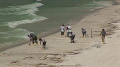 BP Oil Spill workers collection oil on the beach Stock Footage